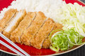 Tonkatsu japanese breaded deep fried pork cutlet on top of boiled rice served with shredded cabbage Stock Photo