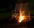 Too close to the fire pair of rocking chairs that have been set afire Stock Photo