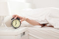 Too early hand under blanket reaching out for alarm clock shallow depth of field focus on foreground Royalty Free Stock Images