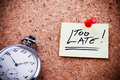 Too late written on a post note and hanged on the cork board with an old pocket watch Royalty Free Stock Photography
