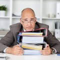 Too much work overworked businessmann leaning head on a stack of binders Stock Images