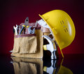 Tool belt hammer yellow helmet red glass background Royalty Free Stock Photography