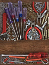 Tool kit among nails and screws against from tree Royalty Free Stock Photo