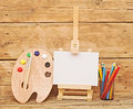Tools for the artist wooden easel with clean paper and wooden artists palette loaded with various colorful paints and pencils Royalty Free Stock Photography