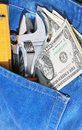Tools and cash in pocket jeans Stock Photo