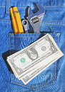 Tools and cash in pocket jeans Royalty Free Stock Image