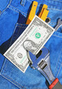 Tools and cash in pocket jeans Stock Photos