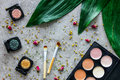 Tools for make up and cosmetics with pallet on gray stone background top view pattern