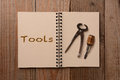 Tools on an open notebook two the blank page of a the opposite page has the word spelled out horizontal format a rustic wooden Stock Photo