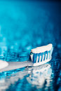 Toothbrush on blue background with water drops Royalty Free Stock Photo