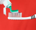 Toothbrush and toothpaste over red background Royalty Free Stock Photo