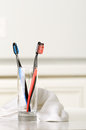 Toothbrushes in a glass and towel on the table selective focus Stock Images