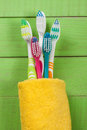 Toothbrushes on the green wooden background