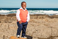 Toothy smile dwarfish african man standing on a big boulder on the rocky beach in stylish clothes smiling whole heartedly Royalty Free Stock Images