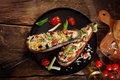 Top down view of a stuffed aubergine with couscous or quinoa on brown vintage wooden background Royalty Free Stock Photos