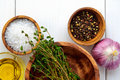 Top flat view of ingredients: salt, pepper, chili,  thyme, garlic, olive oil in bowls on white rustic wooden table Royalty Free Stock Photo