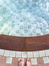 Top of lady feet standing over swimming pool, stair of swimming pool Royalty Free Stock Photo