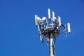 Top part of cell phone communication tower with multiple antennas against a blue sky Royalty Free Stock Photo