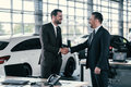 Top sales manager and customer at dealership showroom Royalty Free Stock Photo