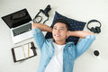 Top view of asian man lying on the floor with laptop, camera, ta Royalty Free Stock Photo