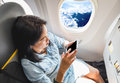 Top view of Asian Woman sitting at window seat in airplane and t Royalty Free Stock Photo