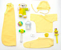 Top view of baby girl yellow clothes and toy stuff Royalty Free Stock Photo