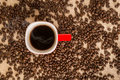 Top view of black coffee in red cup on burlap sack background Royalty Free Stock Photo