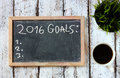 Top view of blackboard with the phrase 2016 goals over wooden board with coffee