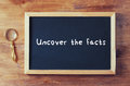 Top view of blackboard with the phrase uncover the facts written on it next to old magnifying glass over wooden table.