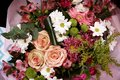 Top view of a bouquet of bright flowers in a pink wrapper