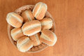 Top view bread rolls in wicker basket on wood table Stock Images