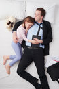 Top view of businessman and his little cute photo tired wearing suit daughter father s arm is over daughter they both sleeping on Stock Photo