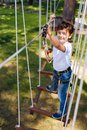 Top view of cheerful preteen boy climbing at rope park Royalty Free Stock Photo