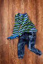 Top view of the children`s clothes and blue toy car on wooden background. Royalty Free Stock Photo