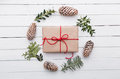 Top view of christmas gift wrapped in craft and decorated with various natural things on white wood Royalty Free Stock Photo