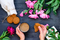 Top view close up female hands holding mug of coffee and cookies surrounded with peonies flowers. Coffee break concept. Selective