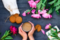 Top view close up female hands holding mug of coffee surrounded with cookies and peonies flowers. Coffee break concept. Selective