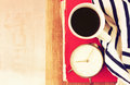 Top view of coffee cup old clock book and blanket over wooden table filtered image Royalty Free Stock Photography