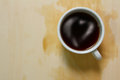 Top view of coffee cup and stains with heart topping on wooden board Royalty Free Stock Photo