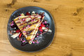 Top view of crepe with chocolate cream, chocolate chips, banana and strawberry served on grey plate Royalty Free Stock Photo