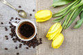 Top view of cup of coffee and bouquet of yellow tulips Royalty Free Stock Photography