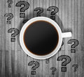 Top view of a cup of coffee and drawn question marks around it on the wooden table. Royalty Free Stock Photo