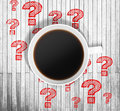 Top view of a cup of coffee and red drawn question marks around it on the wooden table. Royalty Free Stock Photo