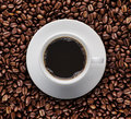Top view of cup of hot coffee on roast coffee bean. Bird eyes view of coffee cup on raw coffee beans. Royalty Free Stock Photo