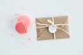 Top view of decorative kraft envelope with bow and pink macarons isolated on white