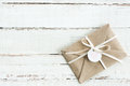 Top view of decorative kraft envelope with tag and ribbon on wooden tabletop