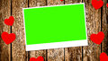 Top view of decorative red hearts with photo frame with chroma key green screen on old wood background Royalty Free Stock Photo