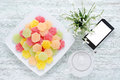 Top view of dessert fruit candy with a phone, coffee pot and fresh snowdrops on vintage wooden table Royalty Free Stock Photo