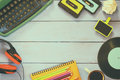 Top view of eighties style objects over wooden table image typewriter cassettes record and headphones Stock Images