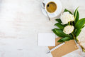 Top view of an empty greeting card, kraft envelope, peonies bouquet and a cup of coffee over white wooden rustic background. Royalty Free Stock Photo